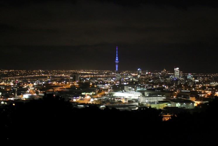 Auckland vom Mount Eden als glitzerndes Lichtermeer. Der Sky Tower sticht blau angestrahlt hervor.