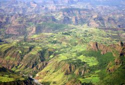 Blick von oben auf eine zerklüftete grün-braune Gebirgslandschaft.