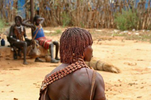 Ein Mann mit dem Rücken zum Bild zeigt seine mit Lehmpaste bearbeitete Frisur.
